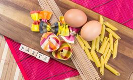 Colorful ravioli pasta with eggs and a pasta sign on a wooden board Stock Images