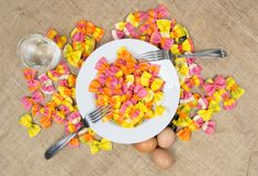 Colorful ravioli pasta with a white plate, two forks, three eggs and a glass of water on canvas Royalty Free Stock Photography