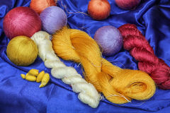 Colorful raw silk thread and silk cocoons. Royalty Free Stock Photo