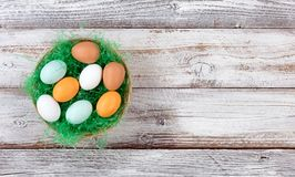Real eggs in basket filled with green grass on rustic white wood Stock Photography