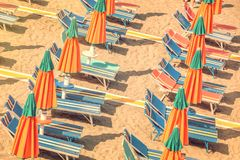 Colorful reclining chairs and parasols on a beach seen from above. Vintage process Stock Image