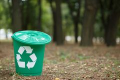 Colorful recycle bin with label in the park without people. Outside photo, land on the background. Stock Photos