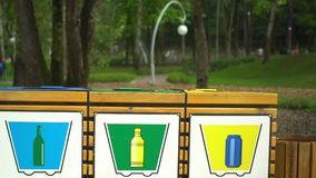 Colorful recycle waste containers bins for separation of garbage in park. Summer stock video