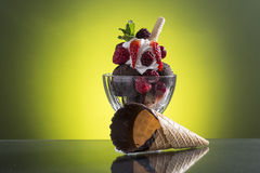 Colorful red berrie cup with chocolate ice and whipped cream Royalty Free Stock Images