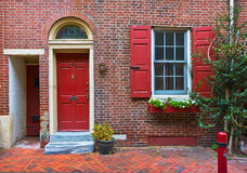 Colorful red door and brick wall Stock Photography