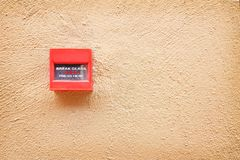 Colorful red fire alarm switch on brown concrete wall , breaking the glass sign background royalty free stock photo