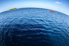 Colorful maldivian dhoni boat floating in wide open ocean with small island in background showing big round world. Colorful red maldivian dhoni boat crosses in Stock Photo