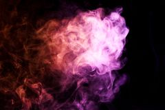 Background from the smoke of vape. Colorful red and  pink a smoke  on a black isolated background. Background from the smoke of vape Royalty Free Stock Image