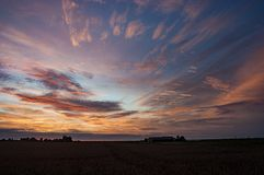Colorful red and pink sunset over a wheatfield in Holland stock photography