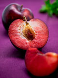 Colorful red plum with mint on purple background Royalty Free Stock Photo