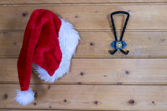 Colorful red Santa Hat hanging on a wall. Colorful red Santa Hat hanging on a hook on a wooden wall in a festive christmas background with copy space stock photography