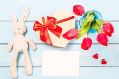 Colorful red spring tulip flowers in nice blue vase, blank photo frame and stuffed toy bunny with decorative heart on light wooden Stock Photography