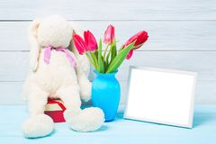 Colorful red spring tulip flowers in nice blue vase, blank photo frame and stuffed toy bunny on light wooden background as greetin royalty free stock image