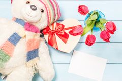 Colorful red spring tulip flowers in nice blue vase, blank photo frame and stuffed toy teddy bear with decorative heart on light w Stock Image
