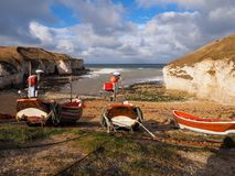 Colorful red and white fishing boats tied up on the beach waiting for the tide to come in with white cliffs. Colorful wooden and red and white fishing boats tied stock photos
