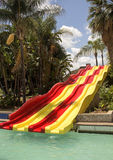 Colorful red and yellow water slide in aqua park. Royalty Free Stock Photos