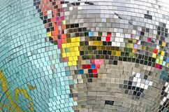 Colorful reflections in a disco ball. Vibrant reflections in the somewhat irregularly placed little square mirrors on a large sphere on a party royalty free stock images