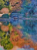 Colorful Monet like reflections at Japanese garden pond with small stone bridge stock images