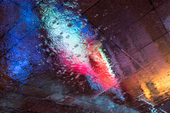 Colorful reflections on wet pavement Stock Photo