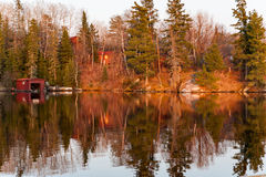 Colorful reflects on a lake. At twilight in Kenora, Ontario stock images