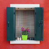 Colorful residential house window in Burano. Traditional colorful residential house window with opened shutters and flower pot in venetian island of Burano Royalty Free Stock Photos