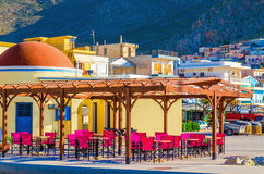Colorful restaurant with red wooden chairs, Greece Royalty Free Stock Photo