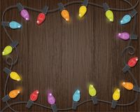 Retro Christmas Lights with Wood Background. Colorful retro style glowing Christmas lights frame on dark brown wood background Royalty Free Stock Images