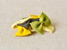 Colorful ribbon shaped pasta. Heap of Italian colorful ribbon shaped pasta on fabric background Stock Image