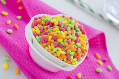 Colorful Rice Cereal on the pink dishcloth with glass of water and straws Royalty Free Stock Photos