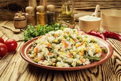 Colorful rice and vegetable salad,Bowl of pasta orzo or rice w. Ith vegetables, selective focus,Appetizing healthy rice with vegetables in plate on a wooden Royalty Free Stock Photography