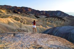 Colorful Ridges landscape with standing attractive young woman open arms wide to feel free, young girl traveler at Death Valley US royalty free stock image