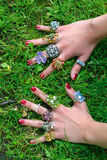 Colorful rings. Girl's hands with many colorful rings on green grass Royalty Free Stock Images