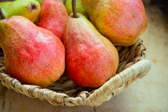 Colorful ripe fresh organic pears in wicker basket on aged wood kitchen table near window Stock Image
