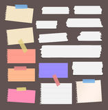 Colorful ripped lined blank note paper, sticky, adhesive tapes are stuck on brown wall Stock Photo