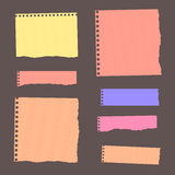 Colorful ripped lined blank note paper are stuck on dark wall Stock Images