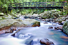 Colorful river with shiny stones running fast under the bridge Stock Photo