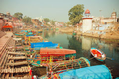 Colorful riverboats floating on the quiet water river of indian city with historical houses Stock Images