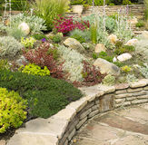 Colorful rock garden with stone wall Stock Image