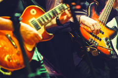 Colorful rock and roll music background. Guitar players on a stage, selective focus and retro tonal correction filter effect, old instagram style Stock Photos