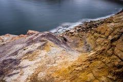 Colorful rocks by frozen reservoir stock photos
