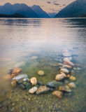 Colorful Rocks in Lake With Background Mountains Stock Photography