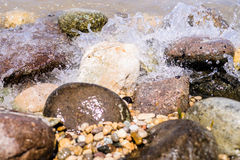 Colorful Rocks with splashing waves on a Beach Royalty Free Stock Image