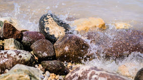 Colorful Rocks with splashing waves on a Beach Stock Images