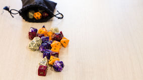 Colorful roleplaying dice scattered on a table with a linen pouch. Closeup photo of colorful roleplaying dice scattered on a table with a linen dice pouch Royalty Free Stock Photography