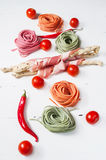 Colorful rolled pasta, cherry tomatoes and bacon on the white wooden background. Royalty Free Stock Photography