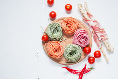 Colorful rolled pasta, cherry tomatoes and bacon on the white wooden background Stock Photos
