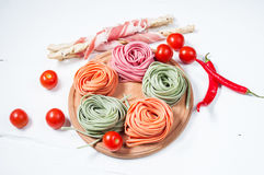 Colorful rolled pasta, cherry tomatoes and bacon on the white wooden background Stock Image