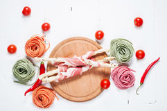 Colorful rolled pasta, cherry tomatoes and bacon on the white wooden background Stock Photography