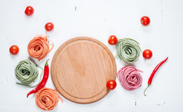 Colorful rolled pasta, cherry tomatoes and bacon on the white wooden background Royalty Free Stock Photography