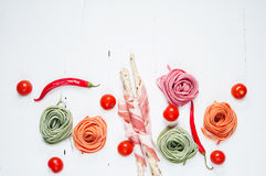 Colorful rolled pasta, cherry tomatoes and bacon on the white wooden background Royalty Free Stock Photos